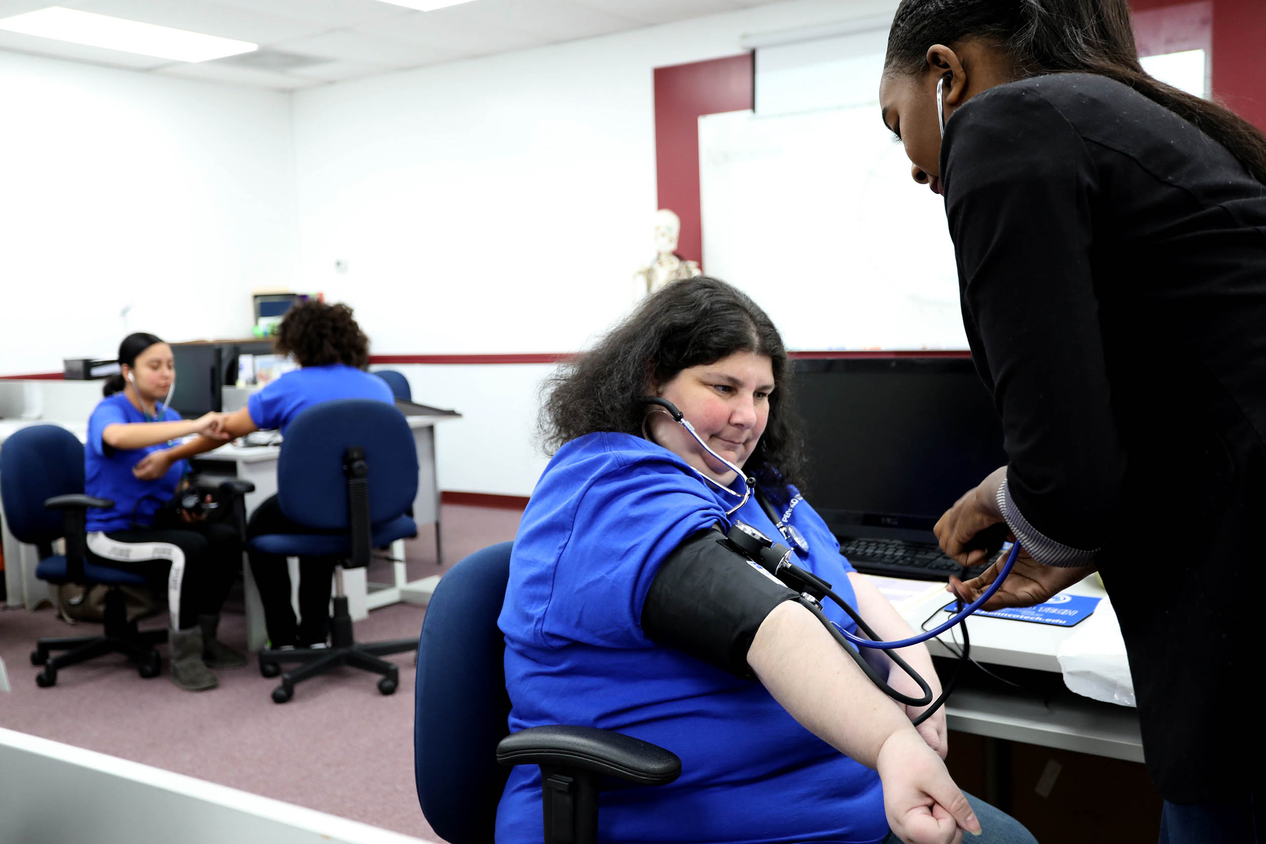 Woman's Heart Rate Being Checked by Medical Assistant Student