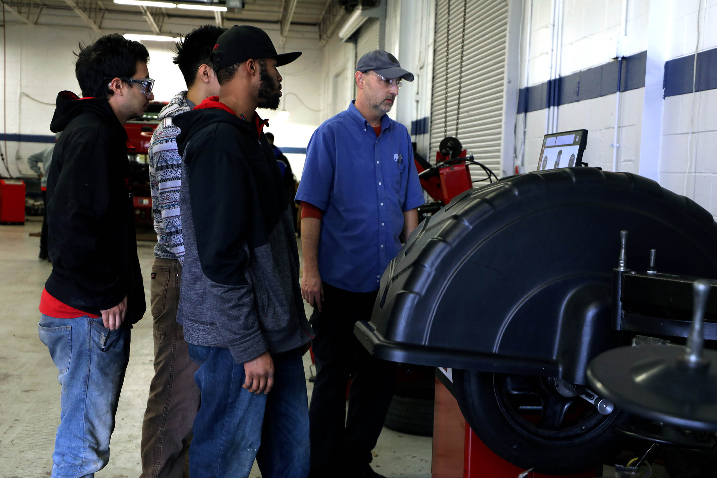 Automotive Instructor Talking to Students About Wheel Well
